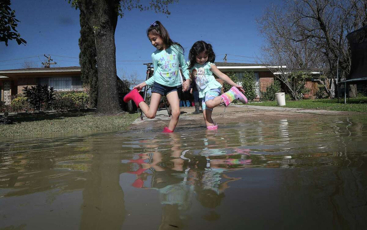 Nemaiah Guadalupe, 8, and Dalliea Silva, 4, attempt to get water out of their shoes as they played in water that rose in their driveway and front lawn near at Clinton and N. Carolina Thursday, Feb. 27, 2020, in Houston.