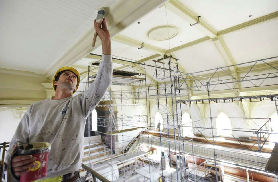 A construction worker touches up pain on the ceiling in the great hall at UPH in Saratoga Tuesday, June 4, 2019. (Photo courtesy UPH/Proctors.)