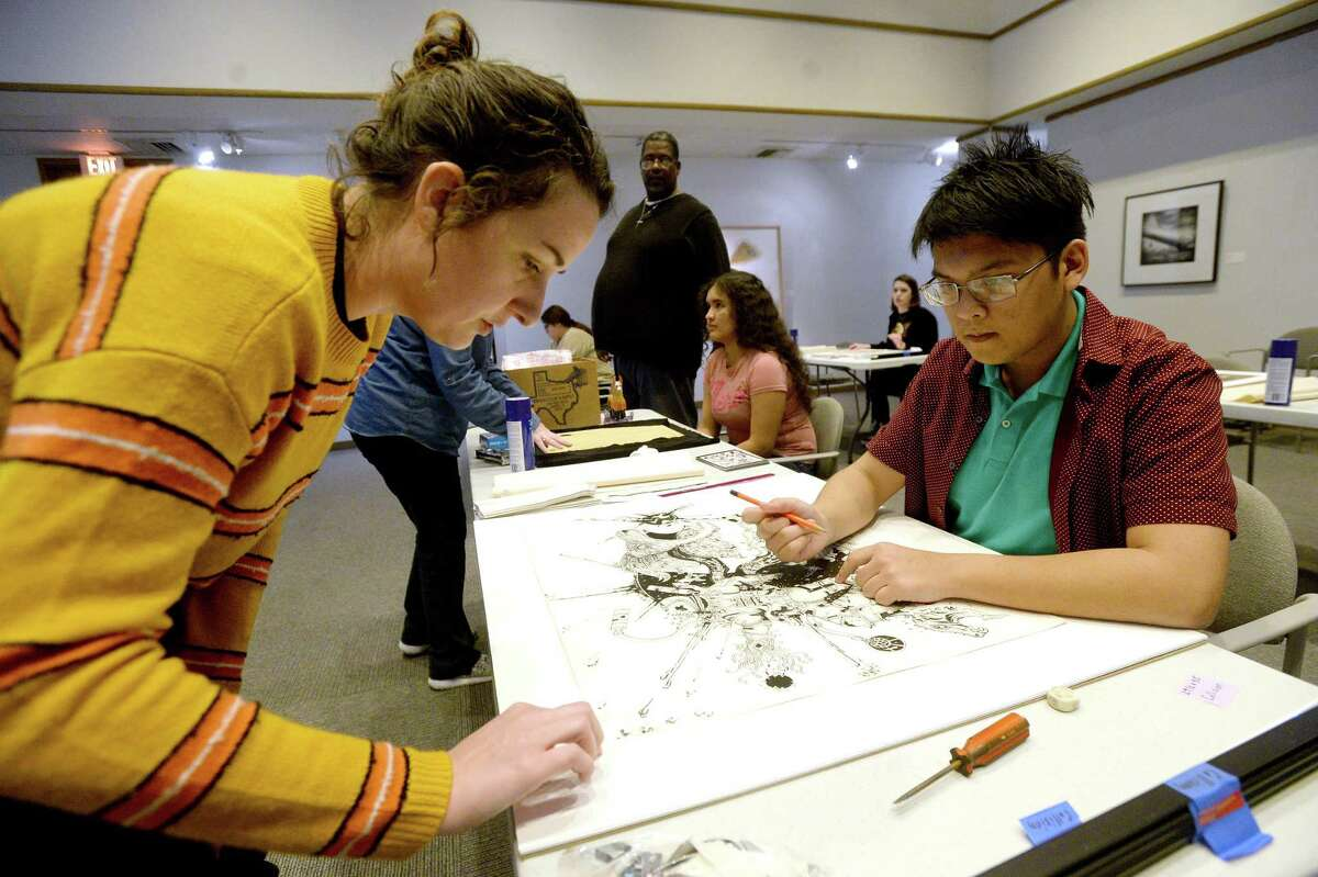 Mariah Rockefeller assists Hull-Daisetta's Lester Fajardo on matting and framing his entry to this year's annual Protege student art show and competition during a workshop held at the Art Museum of Southeast Texas Wednesday. Ninety students submitted work to this year's show, of which 21 were selected for the juried show. Artist Andy Cargill is this year's judge, awarding top prizes, the highest of which is a 4-year scholarship to Lamar University's art program. Student work will be exhibited at the museum through March 28 following the opening reception and award ceremony Thursday, Feb. 27. Thereafter, the show will travel to schools throughout the Golden Triangle. Photo taken Wednesday, February 19, 2020 Kim Brent/The Enterprise
