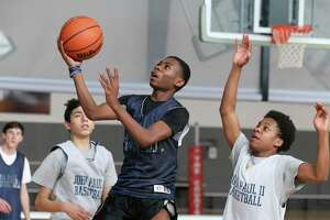 Dezmon Dudley (center) puts up a shot during practice on Wednesday, Feb. 26, 2020. The St. John Paul II Catholic High School men's basketball team is making its TAPPS state-tournament debut on Friday.