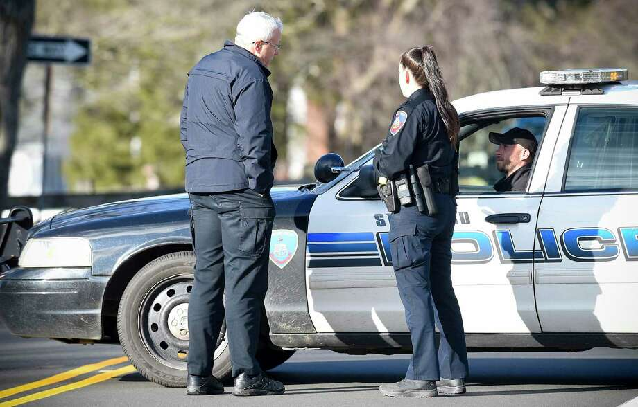Stamford Acting Police Chief Tom Wuennemann, left, talks with officers standing by at a road block on Newfield Avenue near Trinity Catholic High School in Stamford, Conn. on Feb. 27, 2020. Reports of an incident involving an active shooter at a nearby residential home drew a heavy police presence, causing the high school to shelter in place. The initial call was determined to be a hoax, police said. Photo: Matthew Brown / Hearst Connecticut Media / Stamford Advocate