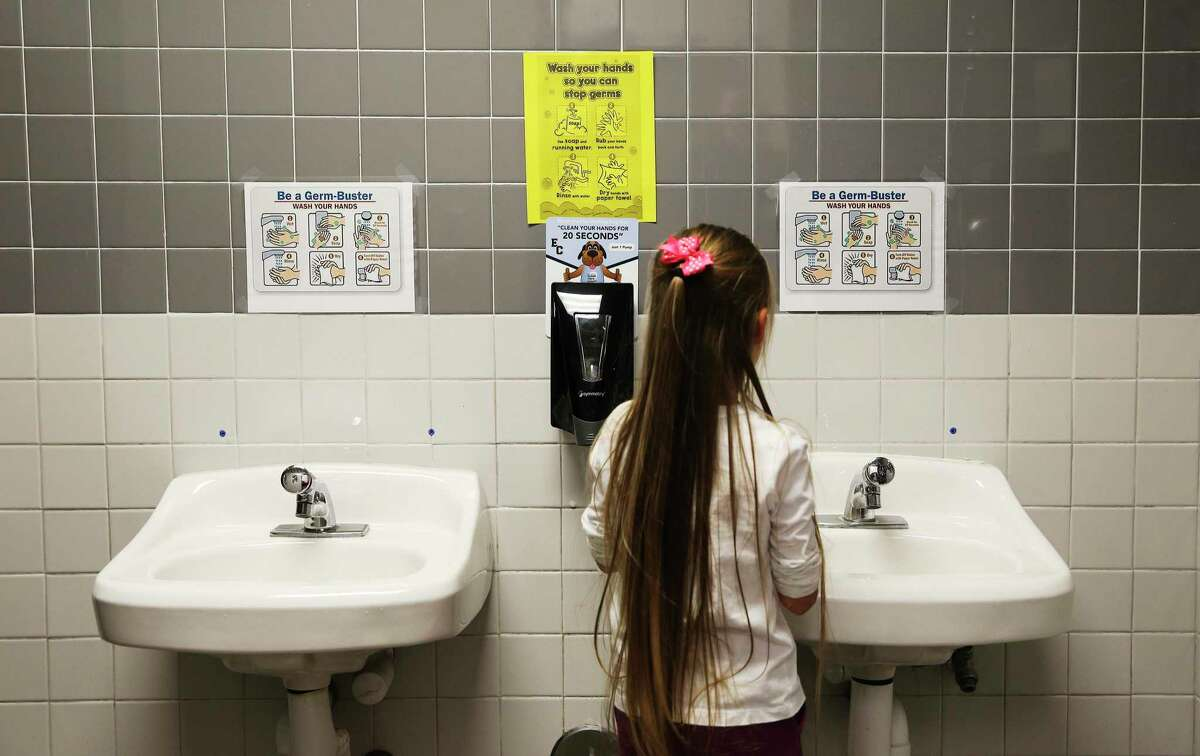 A first-grade student at Oak Crest Elementary in East Central ISD shows how she washes her hands in a bathroom Thursday, Feb. 27, 2020. The school has posted signs in restrooms and one in the main hallway to remind students about hygiene and proper hand washing and the district has sent letters to parents about precautionary measures to guard against coronavirus (COVID-19).