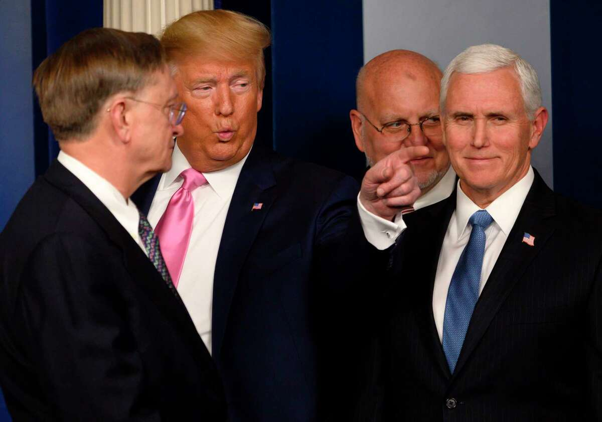 President Donald Trump (2nd L) gestures, flanked by US Vice President Mike Pence (R), after speaking at a news conference on the COVID-19 outbreak at the White House on February 26, 2020. - US President Donald Trump on Wednesday defended his administration's response to the novel coronavirus, lashing the media for spreading panic as he conducts an evening news conference on the epidemic.