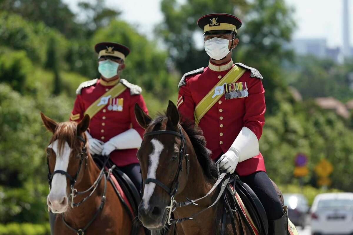 Honor guards wearing protective face masks ride horses patrol outside National Palace, one of a popular tourist spot in Kuala Lumpur, Malaysia, Thursday, Feb. 27, 2020. As the worst-hit areas of Asia continued to struggle with a viral epidemic, with hundreds more cases reported Thursday in South Korea and China, worries about infection and containment spread across the globe.