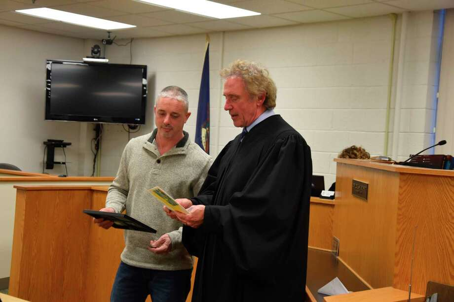 "Chris Gee (left) listens to Judge Thomas Brunner reading a card gifted upon graduation from sobriety court that reads: ""Chris, congratulations on being our very first graduate. You did a great job and are an inspiration to our participants and to our team. Safe travels, gas card enclosed."" (Arielle Breen/News Advocate)"