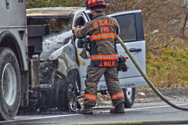 A firefighter from Mitchel Fire Department extinguishes any remaining flames coming from a pick-up truck that was on fire blocking the I-255 northbound exit ramp to New Poag Road Thursday afternoon.