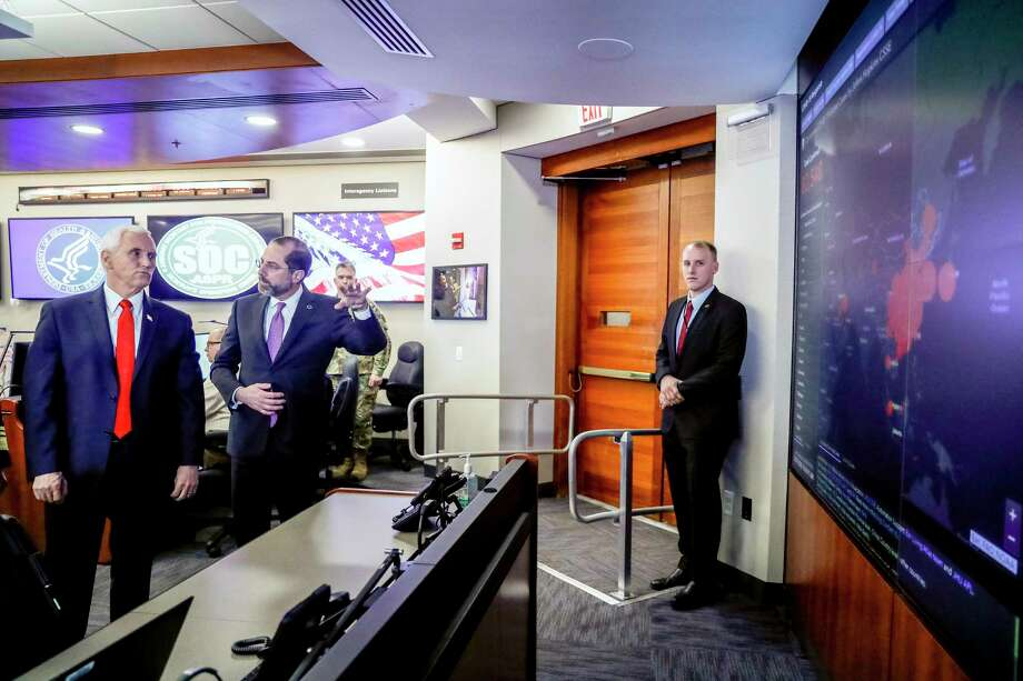 Vice President Mike Pence, left, and Health and Human Services Secretary Alex Azar, second from left, look at a large monitor displaying a tally of total coronavirus cases, deaths, and recovered, as they tour the Secretary's Operations Center following a coronavirus task force meeting at the Department of Health and Human Services, Thursday, Feb. 27, 2020, in Washington. (AP Photo/Andrew Harnik) Photo: Andrew Harnik, STF / Associated Press / Copyright 2020 The Associated Press. All rights reserved