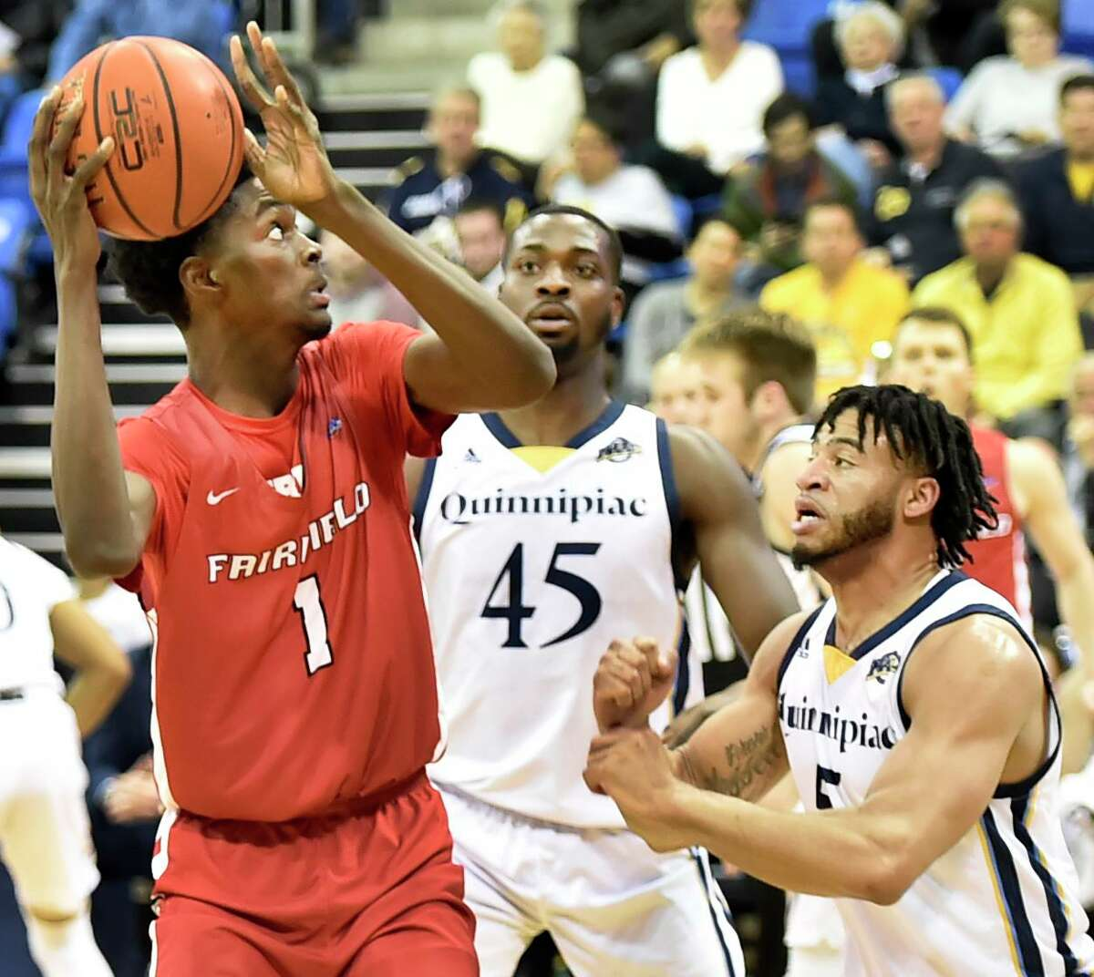Hamden, Connecticut - January 24, 2020: Chris Maidoh of Fairfield University, left, tries to get a shot over Kevin Marfo, center, and Tyrese Williams of Quinnipiac University , right, during first half basketball against Fairfield University Friday at Quinnipiac in Hamden.
