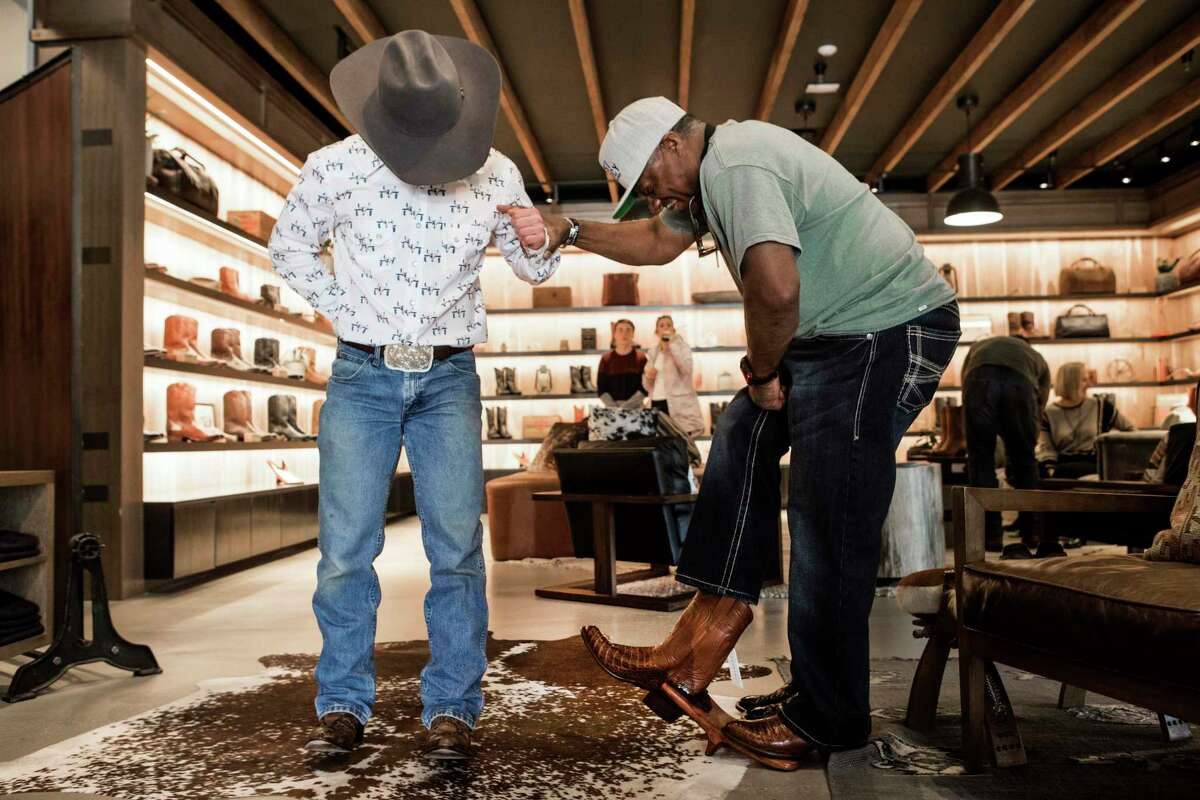 Josh McPherson, left, helps Ricky Williams take off a pair of boots as he shops for a new pair at Tecovas in Rice Village on Tuesday, Feb. 25, 2020 in Houston. With the Houston Livestock Show and Rodeo fast approaching, Houstonians are gearing up for the annual Go Texan Day. You don't have to be born Texan. Anyone can go Texan. It's not about history; it's about attitude and a willingness to play along and belong to the place.
