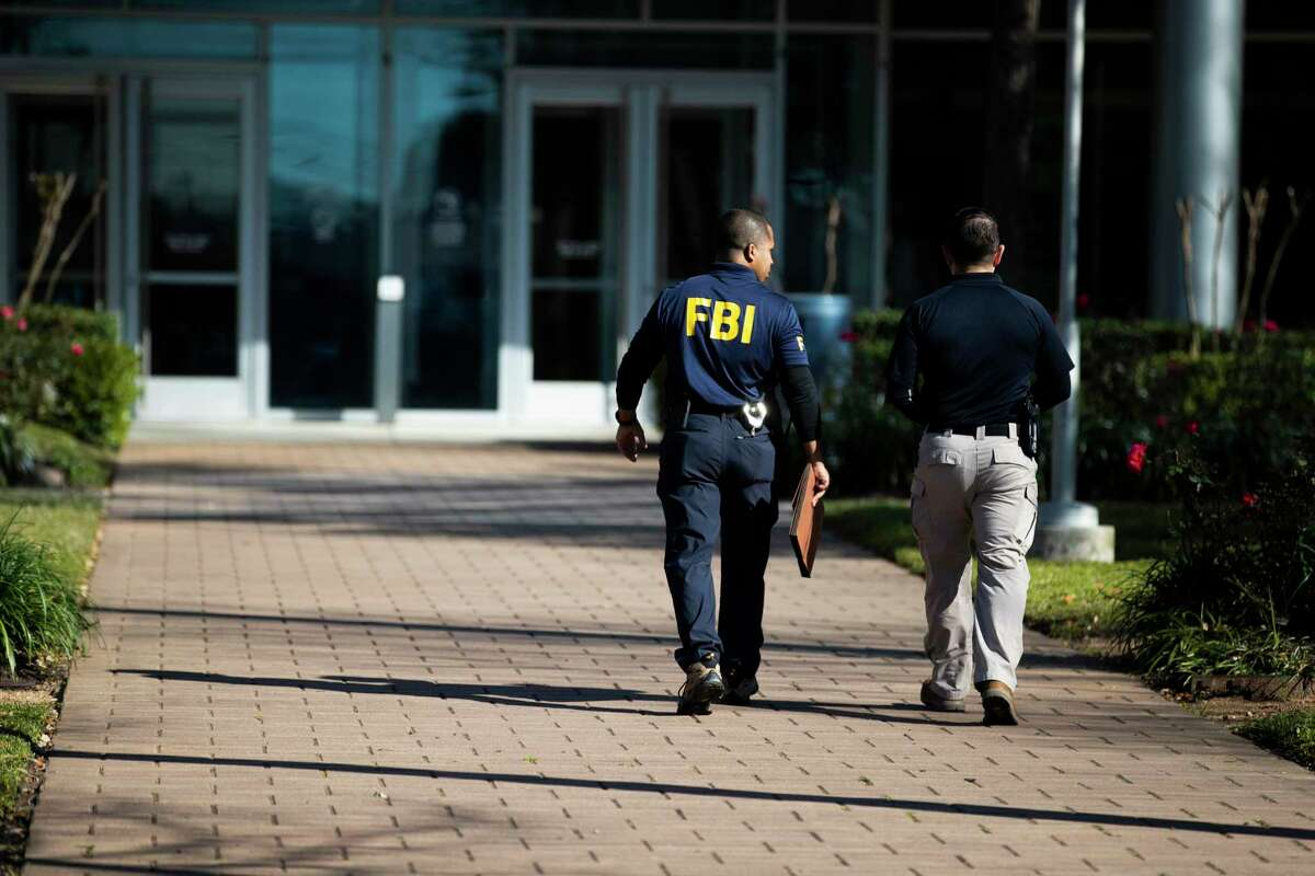 A man wearing an FBI shirt enters Houston ISD headquarters in February, when federal agents raided the office and home of former chief operating officer Brian Busby. Prosecutors allege that Busby engaged in a kickback scheme with a vendor that overbilled the district by $6 million for work it did not perform.