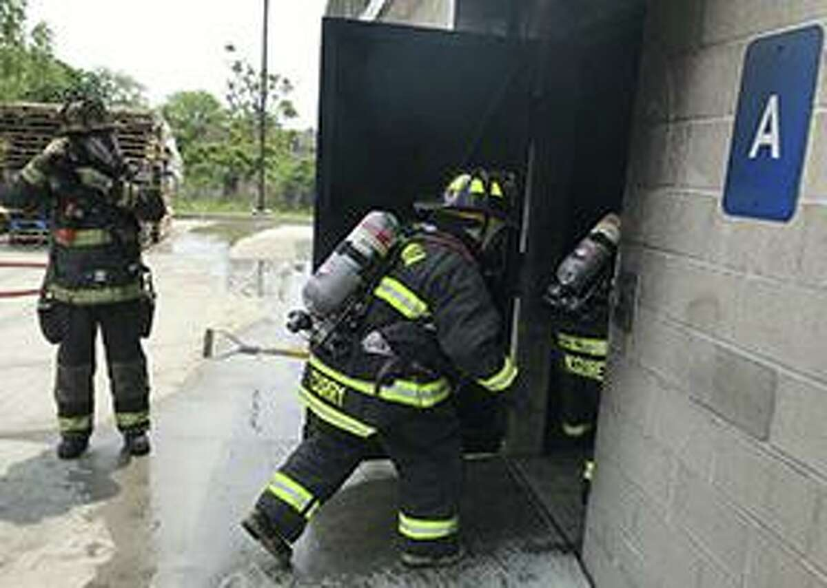 Firefighters enter a building during live burn training.