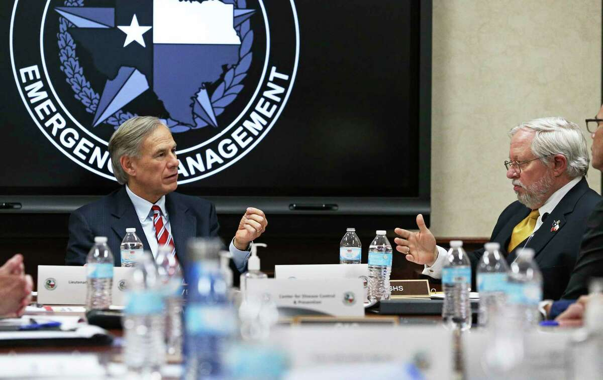 Gov. Greg Abbott asks questions of John Hellerstedt, commissioner of the Texas Department of State Health Services as he meets with public officials at the State Operations Center in Austin on Feb. 27, 2020.