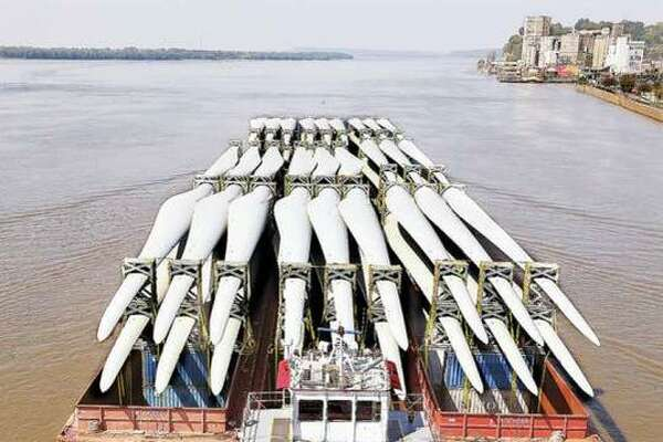 A towboat pushes three barges, loaded with what appear to be 54 blades for wind turbines, under the Clark Bridge in Alton on their way up river.