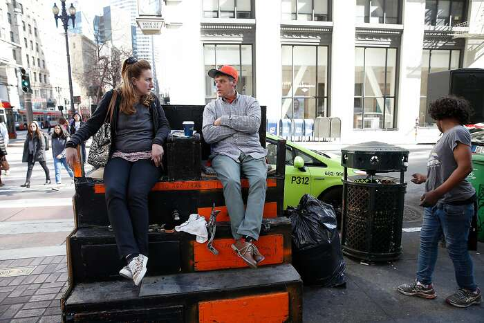 Larry Moore (right) and Allie Manness (left) talk as they sit at Larry's shoeshine stand as a homeless woman looks over the garbage can next to them on Tuesday, February 19, 2020 in San Francisco, Calif. The East Cut Community Benefit District has been trying to get Larry Moore, who has a shoeshine stand outside the Palace Hotel, and his girlfriend into the new Navigation center on the Embarcadero.
