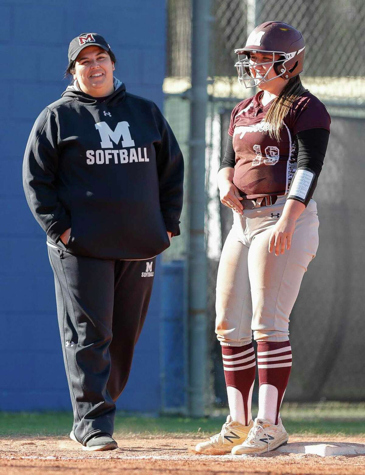 Magnolia head coach Angela Gonzales-Cooper, left, shares a laugh with Caitlyn Stevens during the fourth inning of a non-district high school softball game at Oak Ridge High School, Thursday, Feb. 27, 2020, in Oak Ridge.