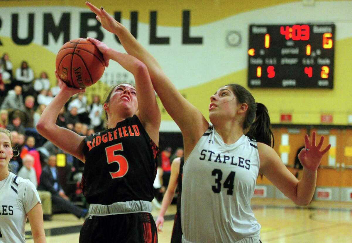 Ridgefield's Cara Sheafe (5) looks to score as Staples' Arianna Gerig (34) defends during FCIAC Girls' Basketball Championship in Trumbull on Thursday. For more information, go to newstimes.com/sports.