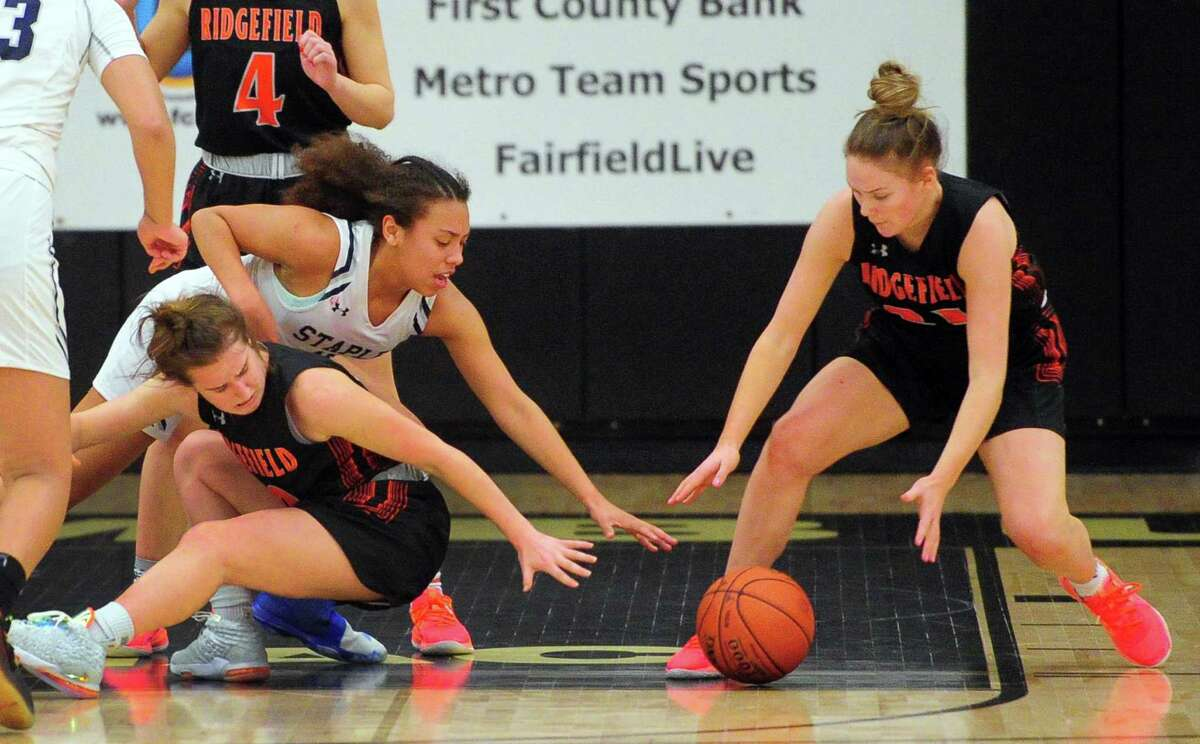 Staples' Nicole Holmes (10), top left, and Ridgefield's Kate Wagner (10) and Cameron McClellan (21), right, reach in for a loose ball during FCIAC Girls' Basketball Championship action in Trumbull, Conn., on Thursday Feb. 27, 2020.