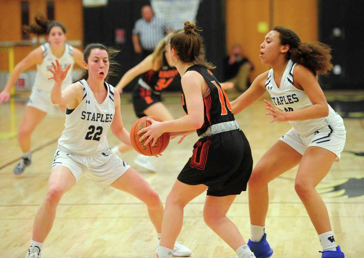 Staples' Kathleen Cozzi (22), left, and Nicole Holmes (10), right, pressure Ridgefield's Kate Wagner (10) as she looks to pass the ball during FCIAC Girls' Basketball Championship action in Trumbull, Conn., on Thursday Feb. 27, 2020.