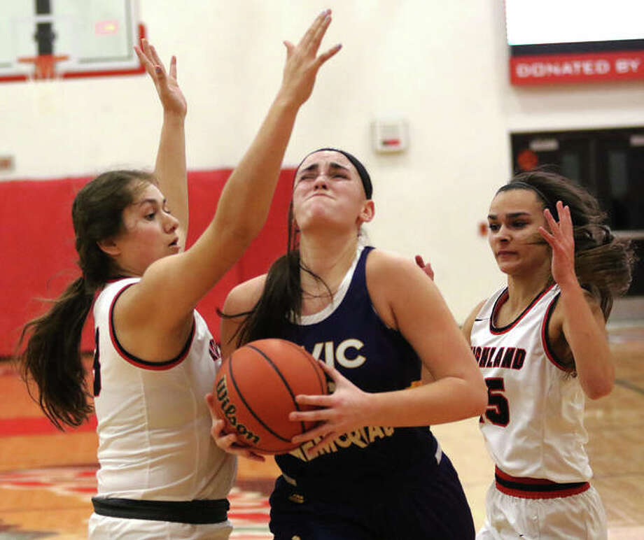 CM's Anna Hall splits Highland defenders Taylor Kesner (left) and Megan Kronk (right) on a drive to the basket Thursday night at the Effingham Class 3A Sectional. Photo: Greg Shashack | The Telegraph
