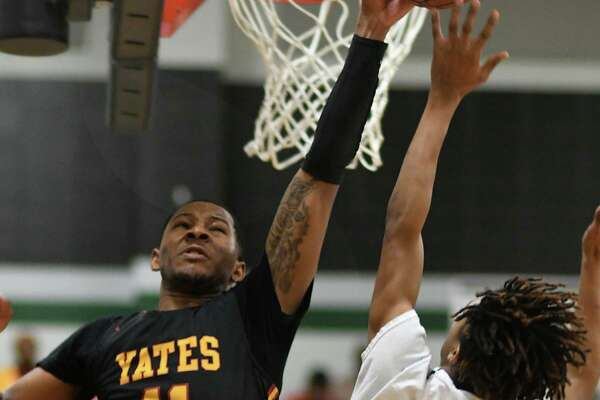 Yates senior guard Elijah Elliott blocks the shot of Hardin-Jefferson's Kam Moore during the Lions' 102-54 victory Thursday night at Kingwood Park High School.