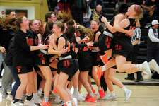 Ridgefield celebrates at the end of its double-overtime win over Staples in the FCIAC girls basketball championship game.