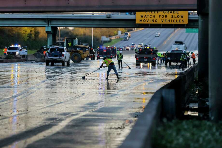 Workers clean water from the southbound lanes of 610 at Clinton Drive, Thursday, Feb. 27, 2020, in Houston. Businesses and schools shut down Thursday after a main line from a plant that supplies water to about half of Houston burst open, submerging vehicles on a flooded freeway and prompting emergency officials to deploy tanker trucks to mitigate any fire hazards. (Mark Mulligan/Houston Chronicle ) Photo: Mark Mulligan Houston Chronicle Staff Photographer / © 2020 Mark Mulligan / Houston Chronicle