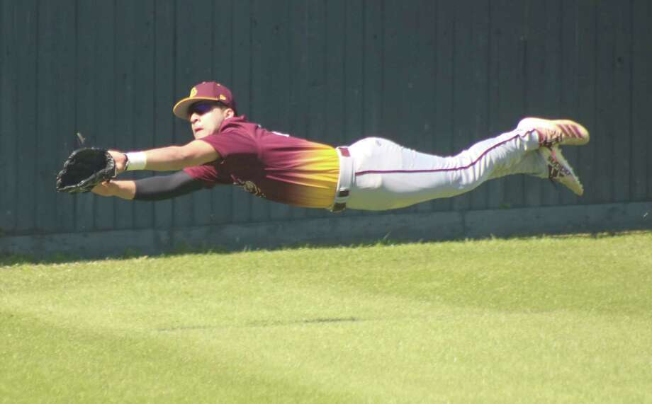 Deer Park left fielder Anthony Solano attempts a diving catch of a foul ball during the Clear Lake game Thursday afternoon. Photo: Robert Avery