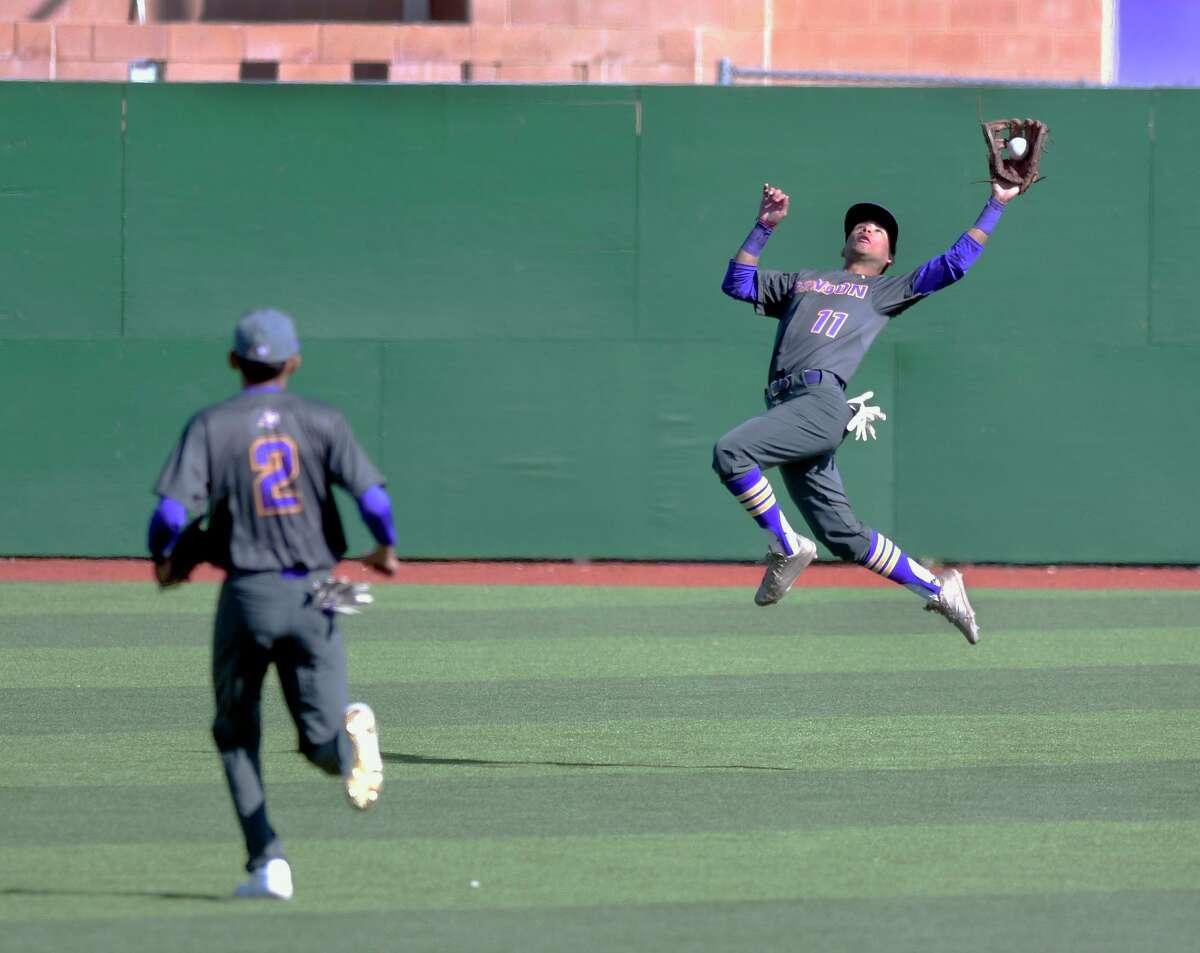 Fernando Garza looks on as his LBJ teammate Mario Espinoza chases down a fly ball.