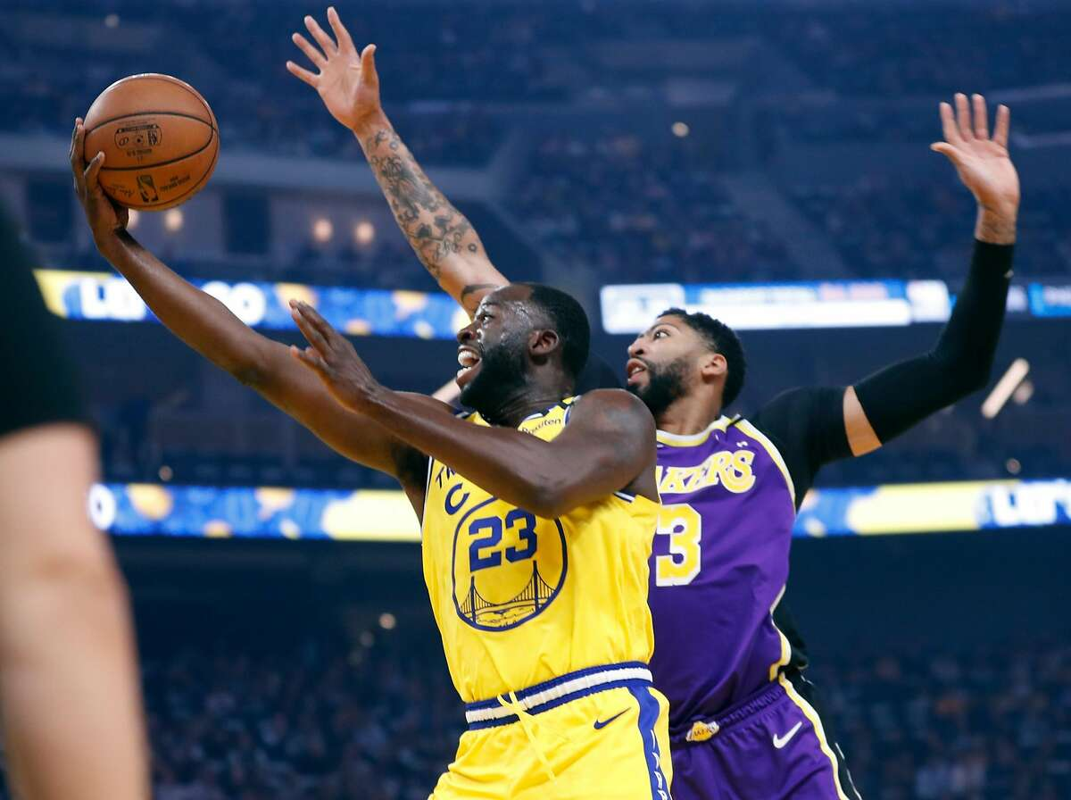 Golden State Warriors' Draymond Green scores past Los Angeles Lakers' Anthony Davis in 1st quarter in NBA game at Chase Center in San Francisco, Calif., on Thursday, February 27, 2020.