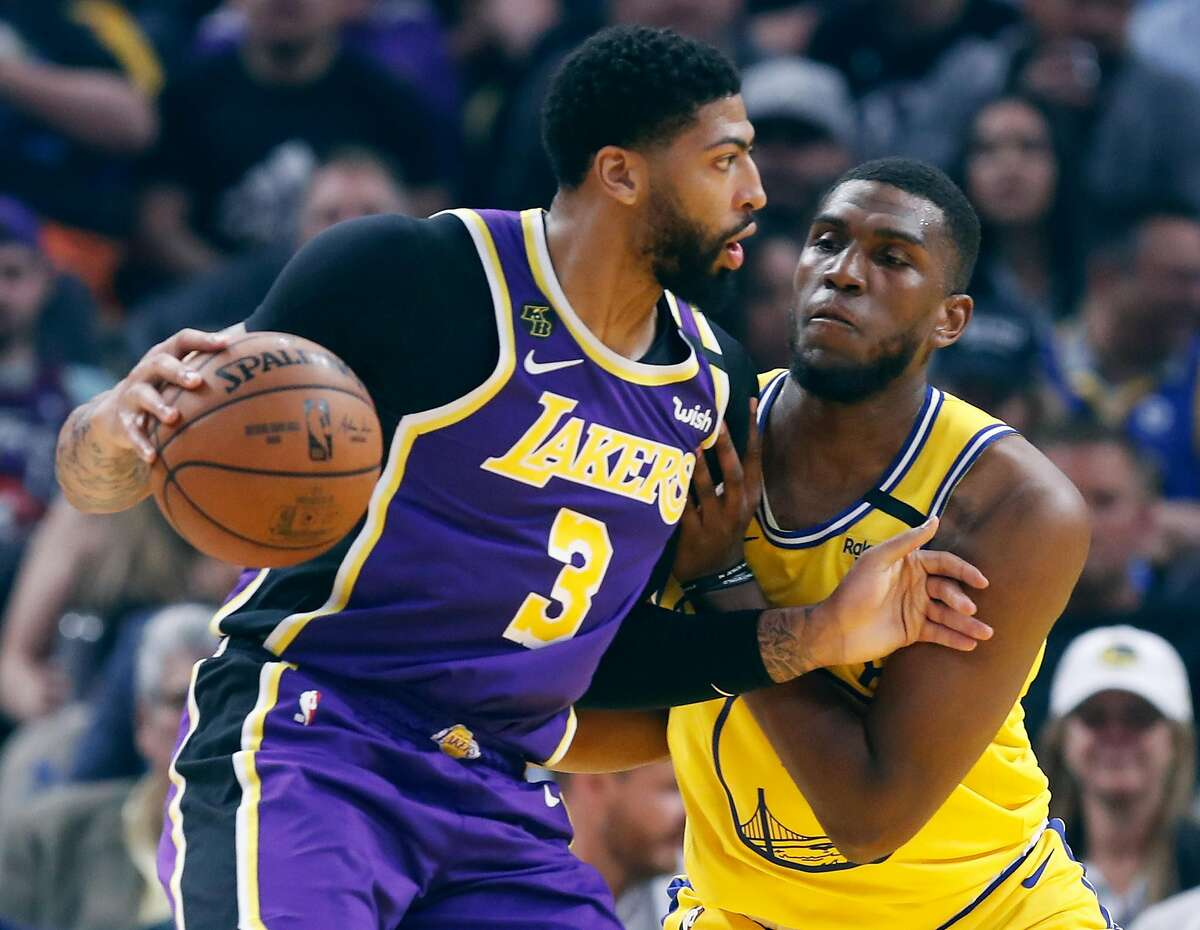 Golden State Warriors' Kevon Looney defends against Los Angeles Lakers' Anthony Davis in 1st quarter in NBA game at Chase Center in San Francisco, Calif., on Thursday, February 27, 2020.
