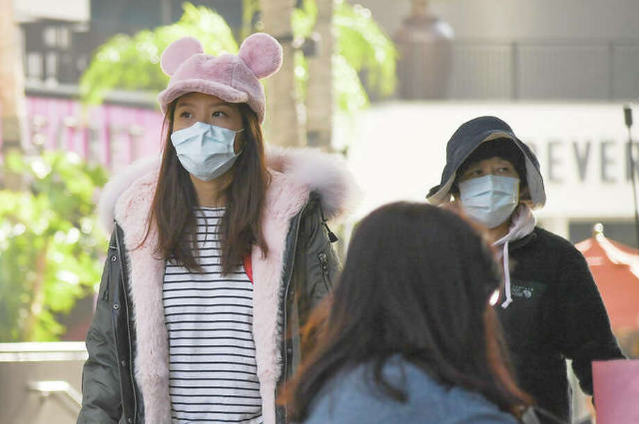 Tourists wear face masks Thursday while visiting the United States.