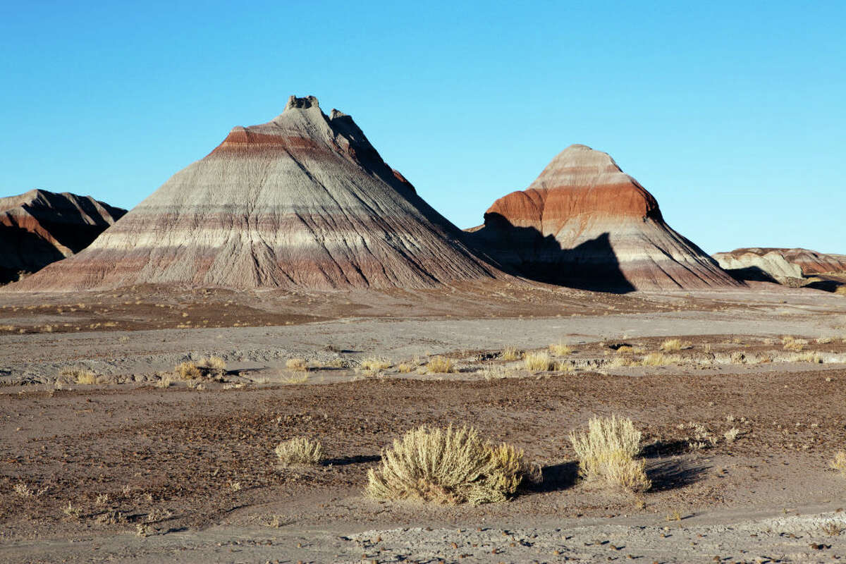 --Petrified Forest National Park -- Painted Desert:The park is in the Arizona desert, about 112 miles east of Flagstaff. It preserves petrified wood dating 225 million years from the Triassic Epoch, plus a fascinating array of petroglyphs.