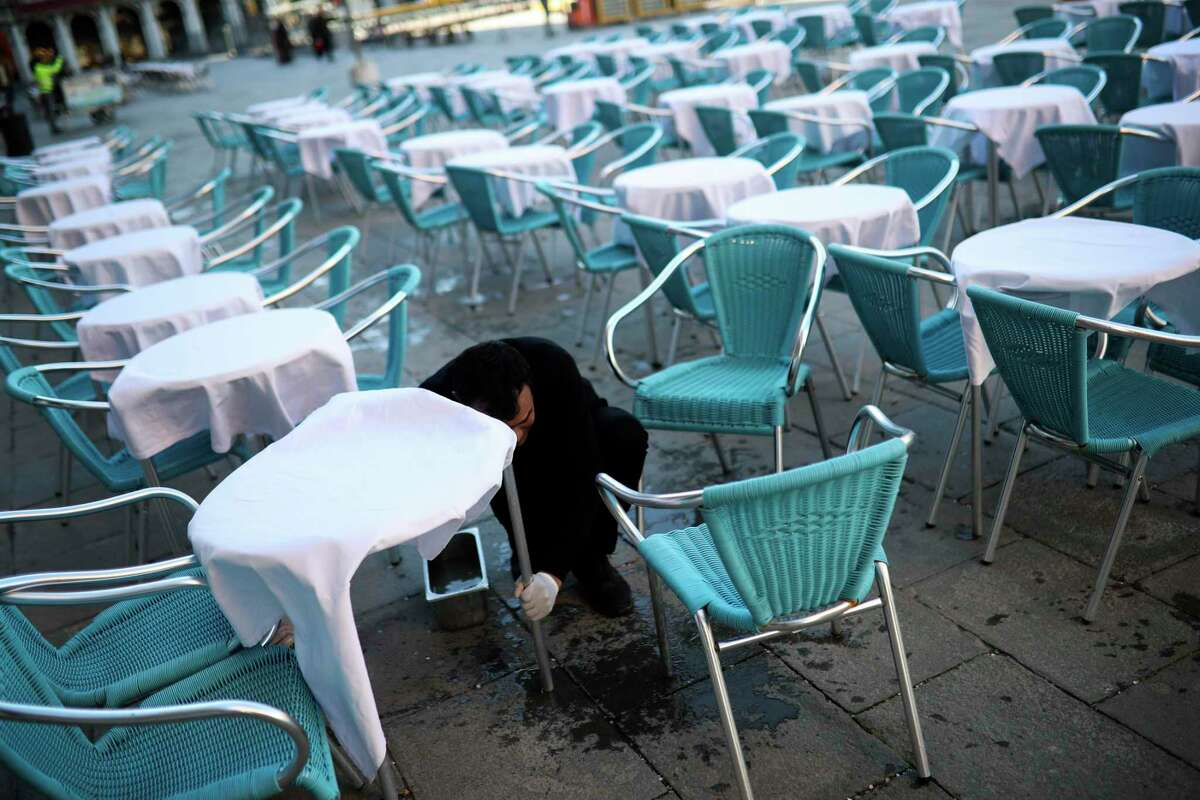 A waiter cleans tables and chairs in an empty restaurant terrace at the St. Mark's Square in Venice, Italy, Friday, Feb. 28, 2020. Authorities in Italy decided to re-open schools and museums in some of the areas less hard-hit by the coronavirus outbreak in the country which has the most cases outside of Asia, as Italians on Friday yearned for a return to normal life even amid fears that the outbreak could plunge the country's economy into recession. (AP Photo/Francisco Seco)