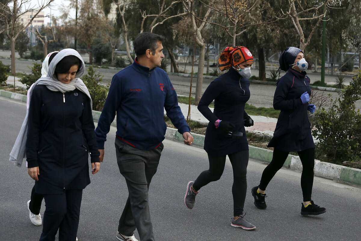 Two women jog with face masks on as others walk while enjoying their weekend afternoon at Pardisan Park in Tehran, Iran, Friday, Feb. 28, 2020. Iranians in Tehran on Friday found time to enjoy their weekend, even as authorities canceled Friday prayers and closed universities, schools and parliament over fears about the new coronavirus.