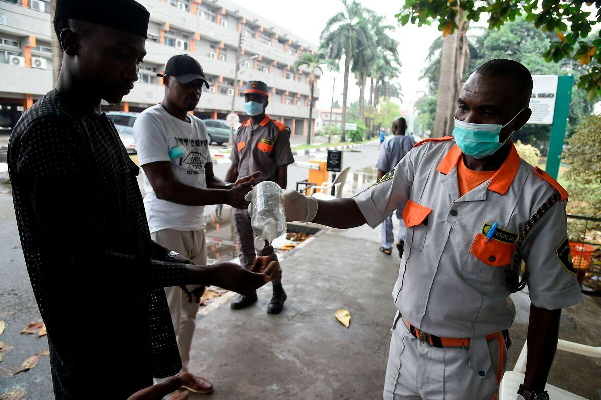 A securityman administers sanitiser to a visitor to a state hospital in Lagos, on February 28, 2020. - Residents of Nigeria's economic hub Lagos scrambled for hygiene products after the chaotic megacity of 20 million announced the first confirmed case of new coronavirus in sub-Saharan Africa. Health Minister Osagie Ehanire said in a statement overnight that the infected person was an Italian citizen who flew in from Milan, at the heart of Europe's largest outbreak, earlier this week.