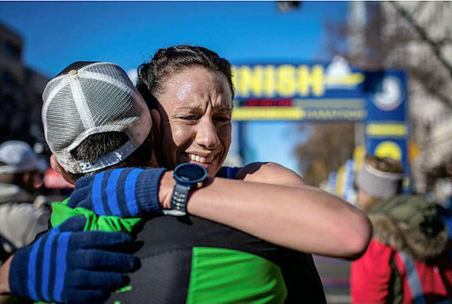 Edwardsville resident Crystal Harriss, right, hugs her coach, James McKirdy, after finding out that her time of 2:44.49 in the California International Marathon on Dec. 2, 2018, qualified her for the U.S. Olympic Marathon Trials, scheduled for Saturday in Atlanta. Photo: Submitted Photo