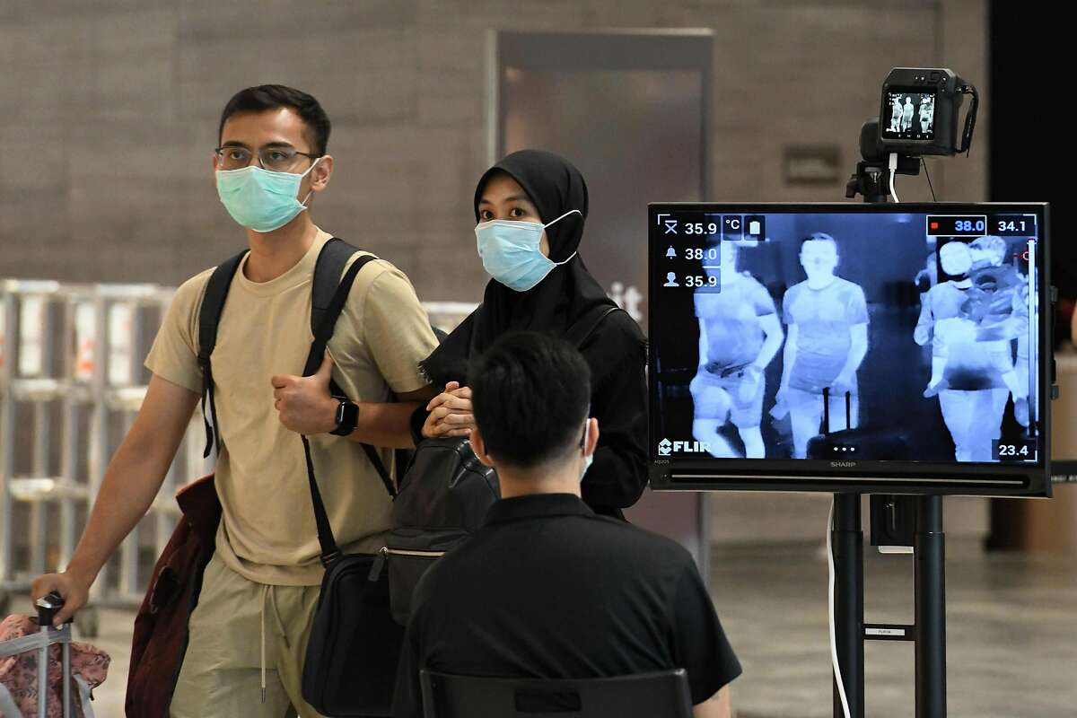 A couple, wearing protective facemasks amid fears about the spread of the COVID-19 novel coronavirus, walk past a temperature screening check at Changi International Airport in Singapore on February 27, 2020. (Photo by Roslan RAHMAN / AFP) (Photo by ROSLAN RAHMAN/AFP via Getty Images)