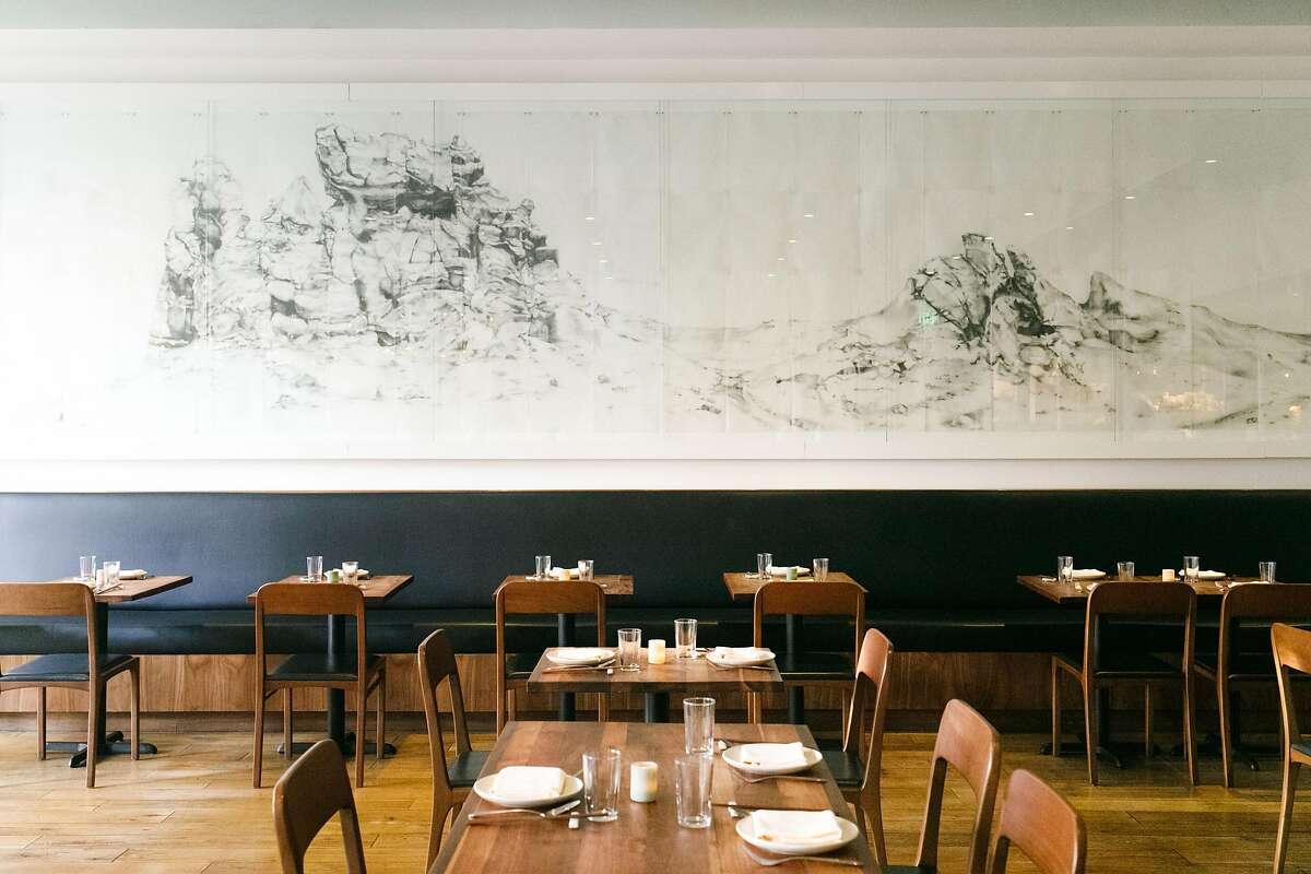 Hand drawn art piece covers the wall in the main dining room at Mister Jiu's in San Francisco.