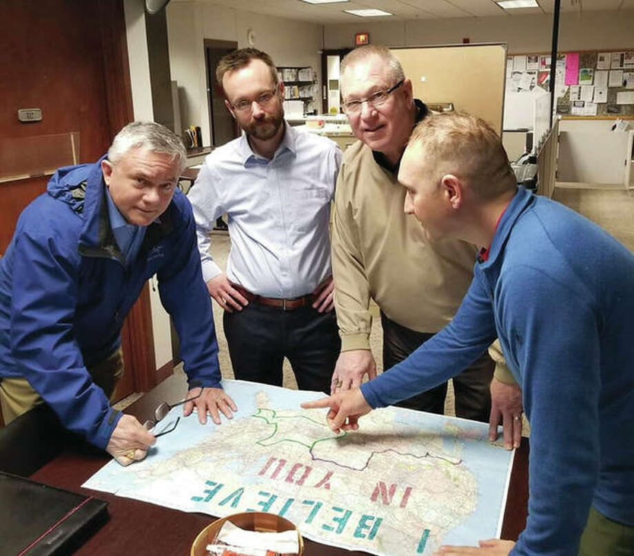 Madison County Board member Don Moore of Troy, left, treasurer Chris Slusser and board member Ray Wesley of Godfrey look at the route Army veteran Steve Meyer is taking on across the county to raise awareness for post-traumatic stress disorder.