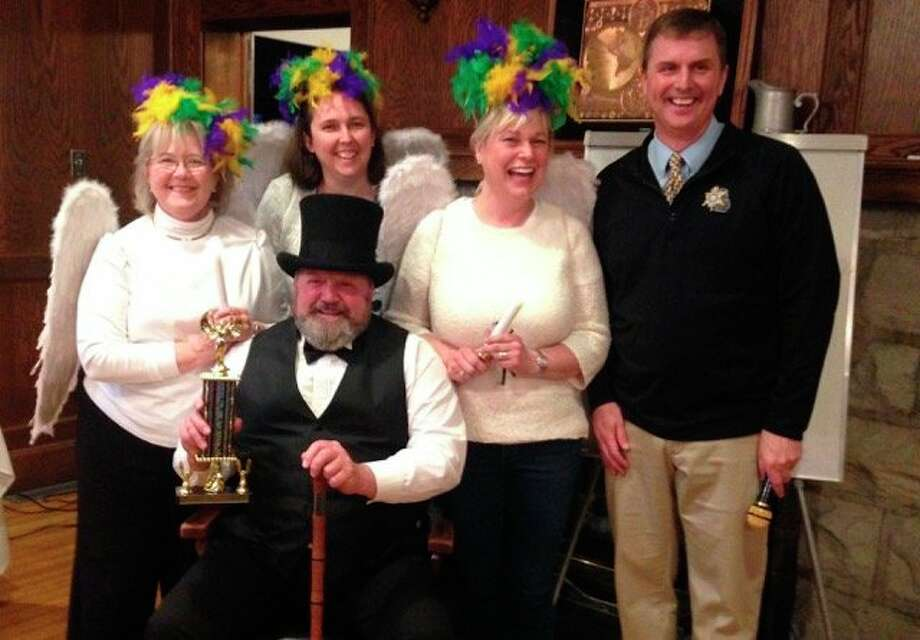 """In 2019, the first place winner of the League of Women Voter's Pictionary Olympics was the Charlie's Guardian Angels; the group also won """"Best Costume."""" Pictured is the emcee Manistee County sheriff John O'Hagan, and the Charlie's Guardian Angels teammates. (Courtesy Photo)"""