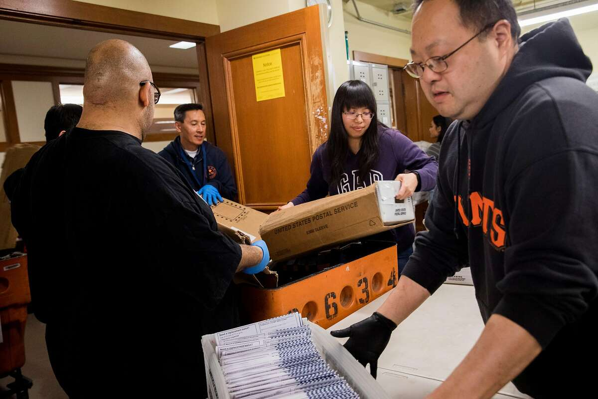 (From left) Election staff members Michael Bitanga, Alice Law and Stephen Wong work to sort out vote-by-mail ballots that arrived in the mail ahead of the March 3rd election at San Francisco City Hall in San Francisco, Calif. Friday, February 28, 2020.