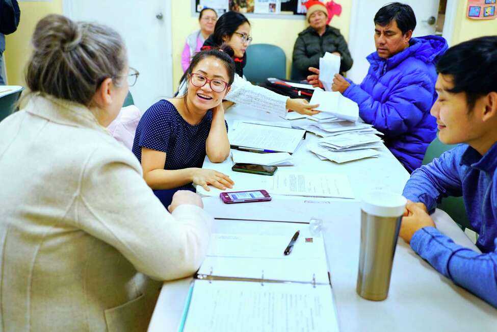 Karen refugees from Burma, Shae Paw, center, and her husband, Dou Dou, work with Susan Kukuk, left, a co-founder of the Refugee Community Health Partnership of Trinity Alliance, during their quick help walk-in session on Tuesday, Feb. 19, 2020, in Albany, N.Y. The nonprofit group holds their quick help session every Tuesday morning. (Paul Buckowski/Times Union)