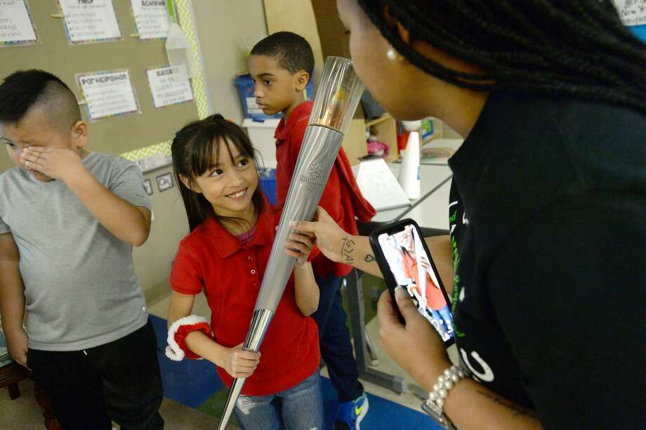 Chyler Masilang smiles as she gets a chance to hold the Olympic torch Vicki Baumgartner carried in the relay leading up to the 2002 Olympics in Salt Lake City. Baumgartner brought mementos and more for her visit to Courtney Cumby's first grade class at Regina - Howell Elementary School Friday. In addition to sharing photos of her participating in the run, Baumgartner read a story about the Olympics and brought hands-on activities for the class. Photo taken Friday, February 28, 2020 Kim Brent/The Enterprise Photo: Kim Brent/The Enterprise