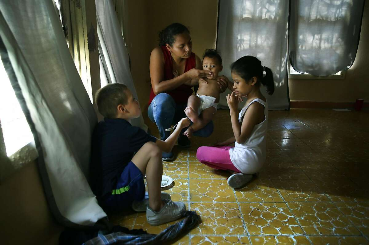 Mariluz Calderon, mother of 4 kids, from Nicaragua, feeds her youngest, Braulio, from a plate of rice in the Good Samaritan Shelter in Nuevo Laredo. Migrants from Central America and Cuba go to asylum hearings in Laredo, Texas, on Thursday, Sept. 19, 2019.