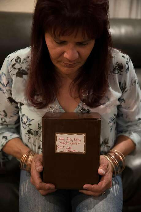 Melissa Moore, ex-fiance of Kelly Gene Perry, holds a container with his ashes at her home in Castro Valley, Calif., on Tuesday, February 18, 2020.  Perry's body was recently identified through forensic genealogy after his dismembered body was found 22 years ago in Livermore months after he went missing. The body was too decomposed to be identified until new technology allowed a positive match, and police are reexamining the cold case following the identification. Photo: Carlos Avila Gonzalez / The Chronicle