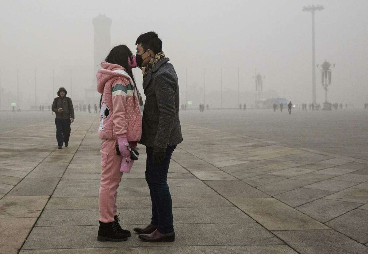 A Chinese couple kiss through masks during a polluted day in 2015. Responding to a letter writer who pointed out that China is working to reduce carbon emissions, a reader wonders why it's taken this long.