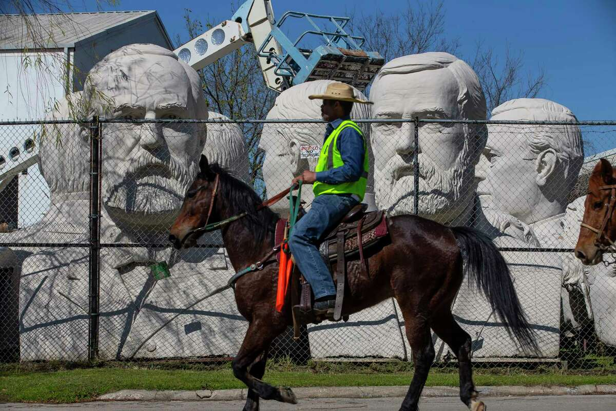 Riders with the Northeastern Trail Ride pass David Adickes studio on Nance Street on their final day of a seven-day-long trail ride that started near Beaumont, Friday, Feb. 28, 2020, in Houston.
