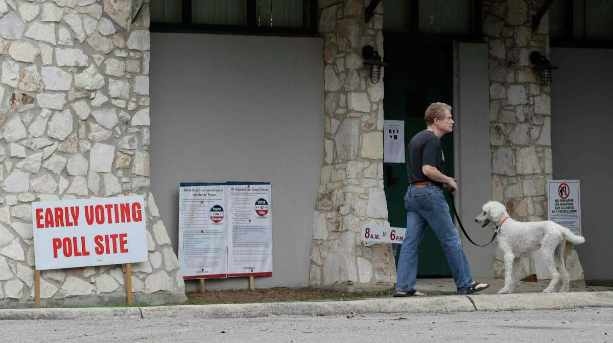 A man and his dog pass outside of a voting site in San Antonio, Tuesday, Feb. 18, 2020. Early primary voting for began Tuesday for Texas and Arkansas ahead of Super Tuesday. (AP Photo/Eric Gay)