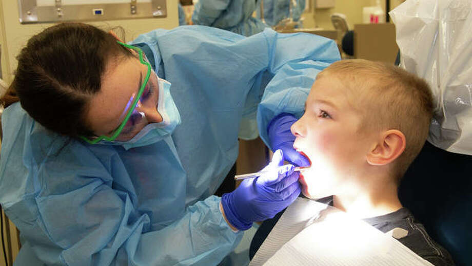 A fourth-year SIU School of Dental Medicine student in Alton performs a non-invasive screening on a second grade student during a National Children's Dental Health Month event.