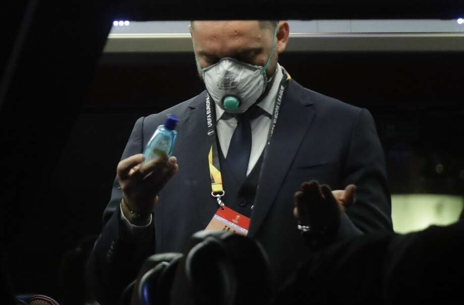 A Bulgarian soccer team staffer disinfects his hands on a coach bus heading to the San Siro stadium Milan, Italy, Thursday. Ludogorets is playing Italian club Inter Milan in a Europa League soccer match on Thursday that is scheduled to go ahead in an empty stadium due to the coronavirus outbreak. Photo: (AP Photo/Luca Bruno) / Copyright 2020 The Associated Press. All rights reserved